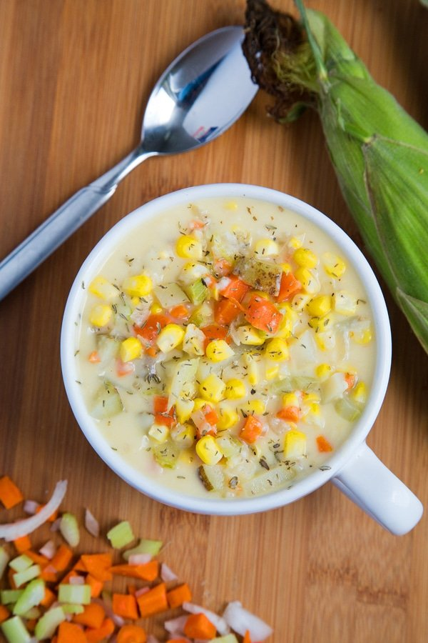corn chowder in a large white mug with ears of corn , cut carrots, onions and celery all sitting on a cutting board with a spoon next to the cup of chowder