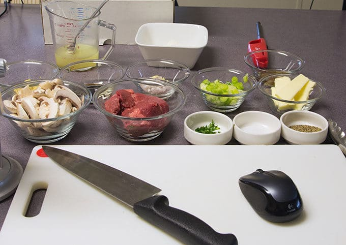 ingredients to make steak Diane, with a knife and wireless mouse on a white cutting board