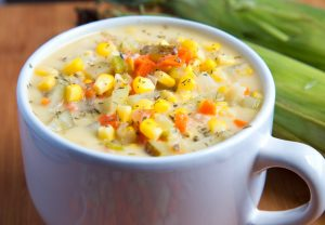 corn chowder in a large white mug with ears of corn in the background