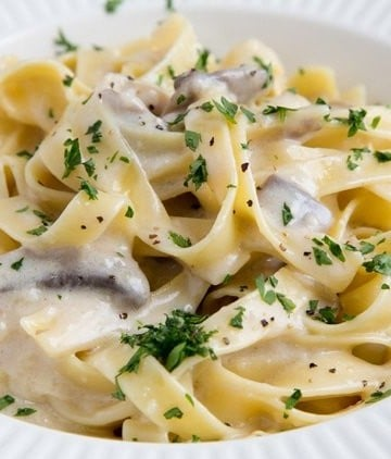 fettuccine alfredo in a white bowl sprinkled with parsely