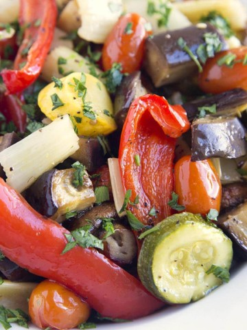 a white bowl full of roasted vegetables