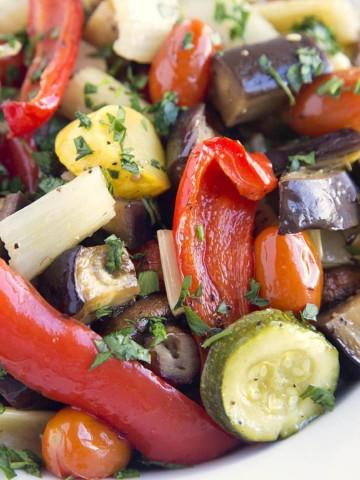 a white bowl full of roasted vegetables