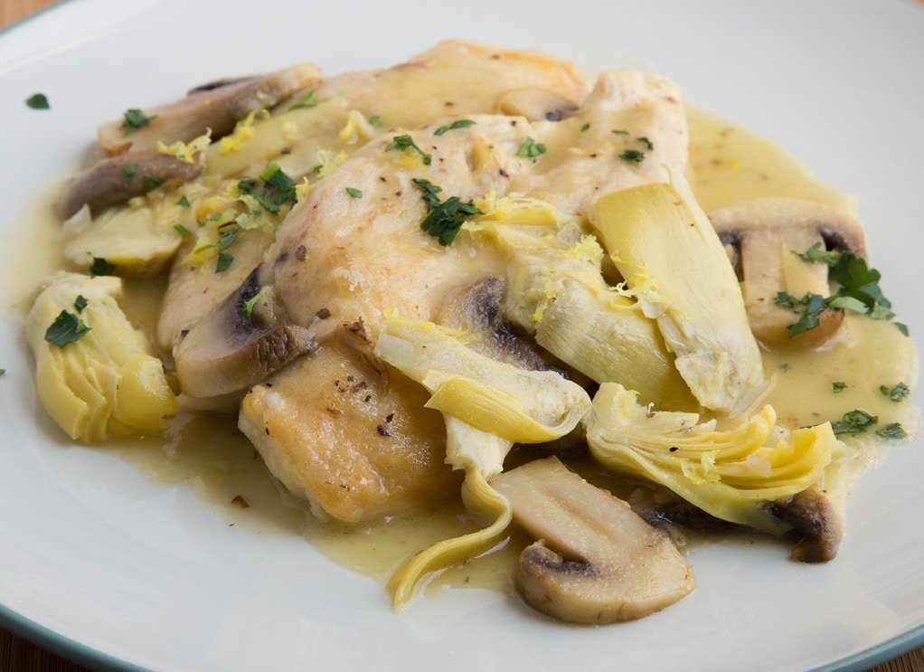 side view of chicken picante with mushrooms and sliced artichoke hearts on a white plate