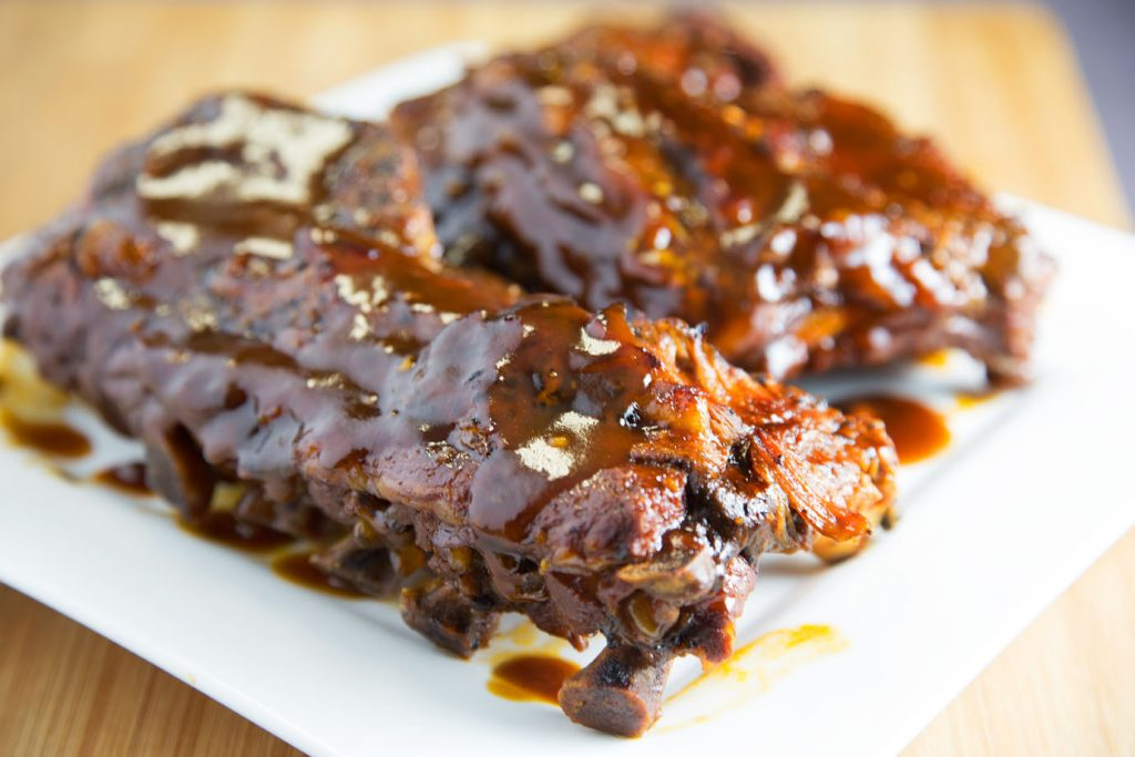 side view of rack of Ginger Beer Barbecue Ribs on a white plate