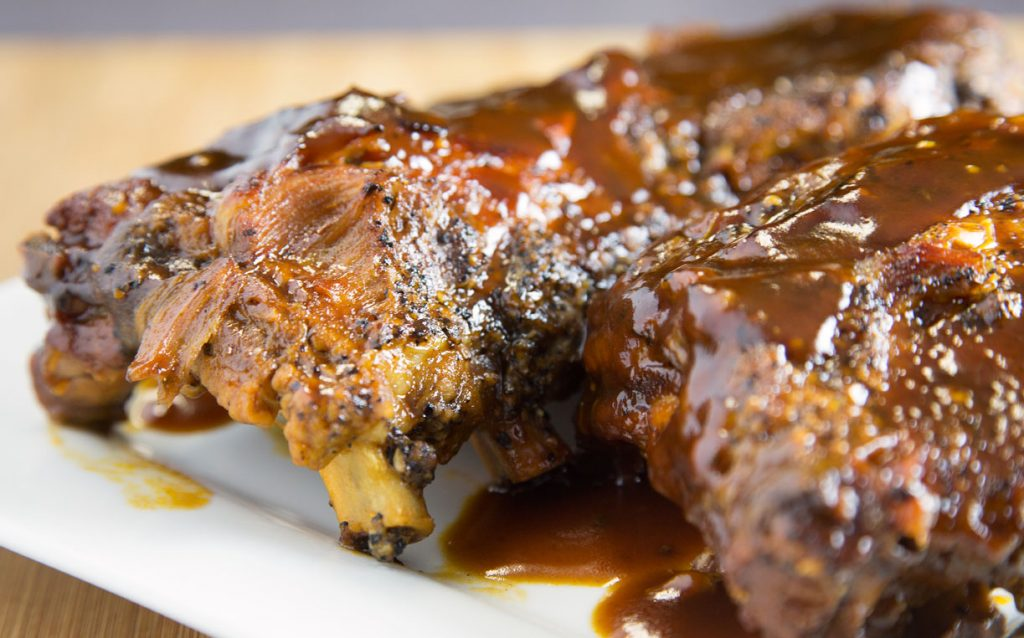 Side view of Ginger Beer Barbecue Ribs on a white plate