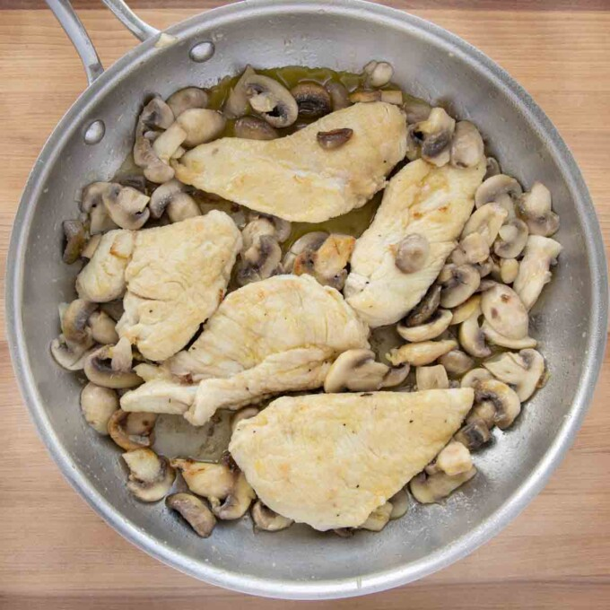 mushrooms and shallots sauteed with the chicken in a pan