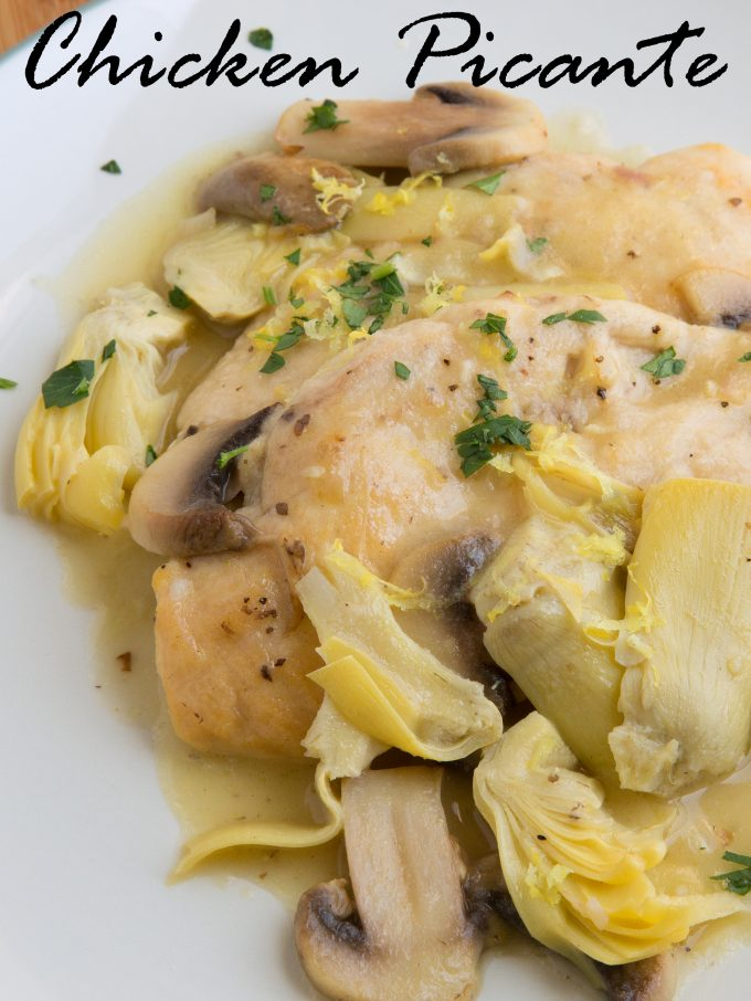 close up view of chicken picante with mushrooms and sliced artichoke hearts on a white plate
