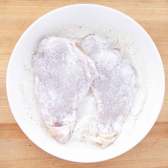 chicken coated in flour in a white bowl of flour