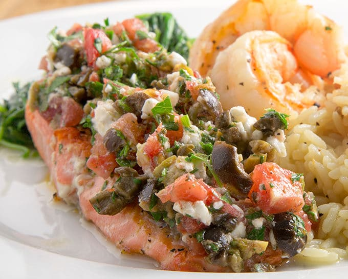 salmon topped with a tapenade served on a white plate with shrimp