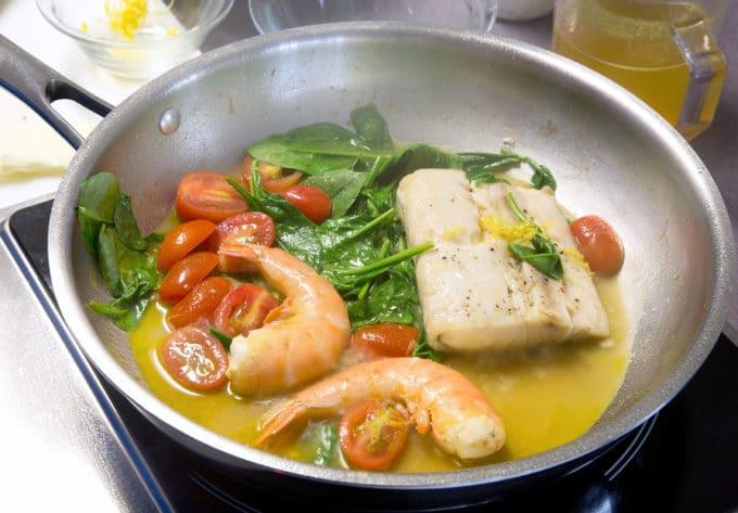 mahi, spinach, grape tomatoes and shrimp cooking with mahi-mahi in a saute pan with a court boullion