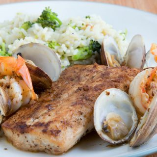 blackened fish, clams and shrimp on a white plate with rice and broccoli
