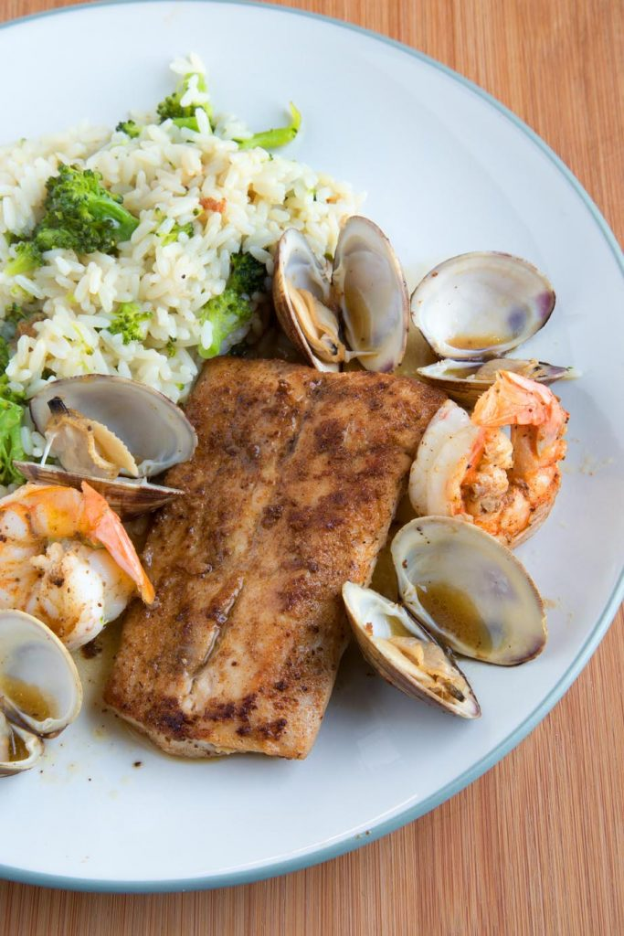 overhead view of Baltimore Clam Bake with blackened fish, clams and shrimp on a white plate with rice and broccoli