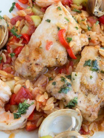 overhead shot of Chicken and Shrimp Orzo Paella on a white plate