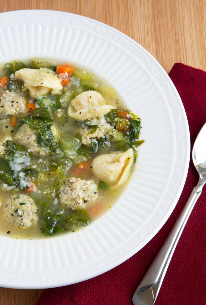 overhead partial view of White bowl of Italian wedding soup with a spoon sitting on a dark red napkin