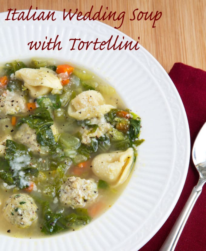 White bowl of Italian wedding soup with a spoon sitting on a dark red napkin
