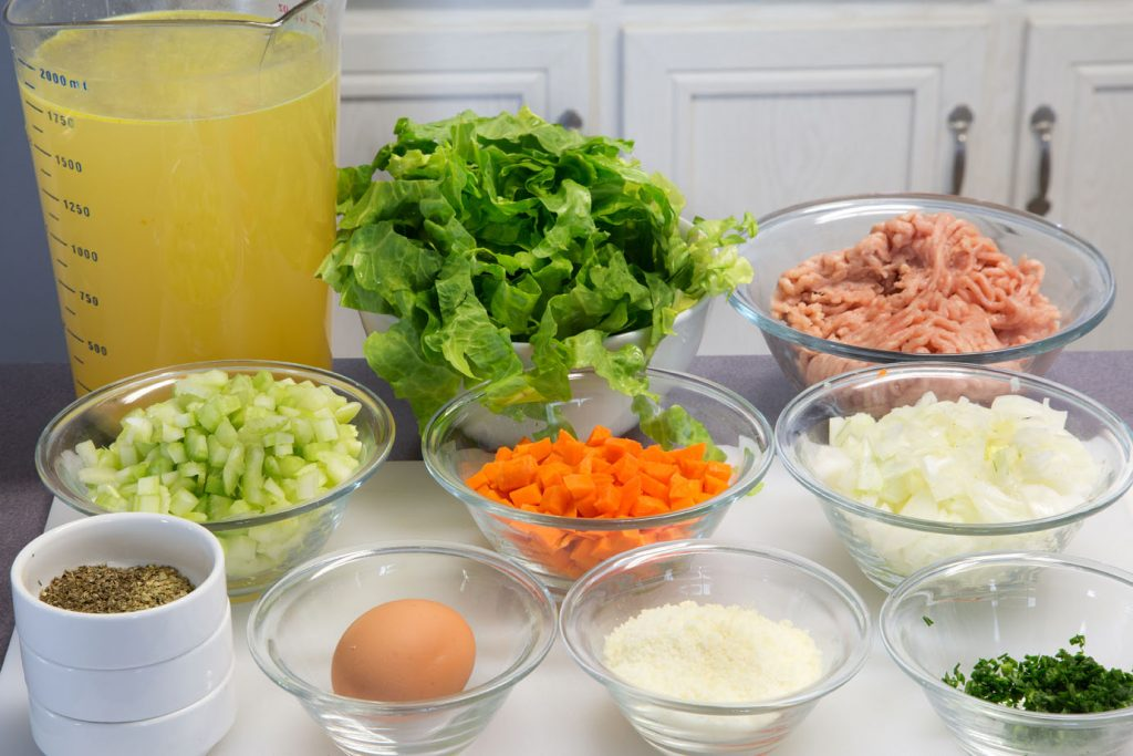 ingredients to make Italian Wedding Soup in bowls on a white cutting board