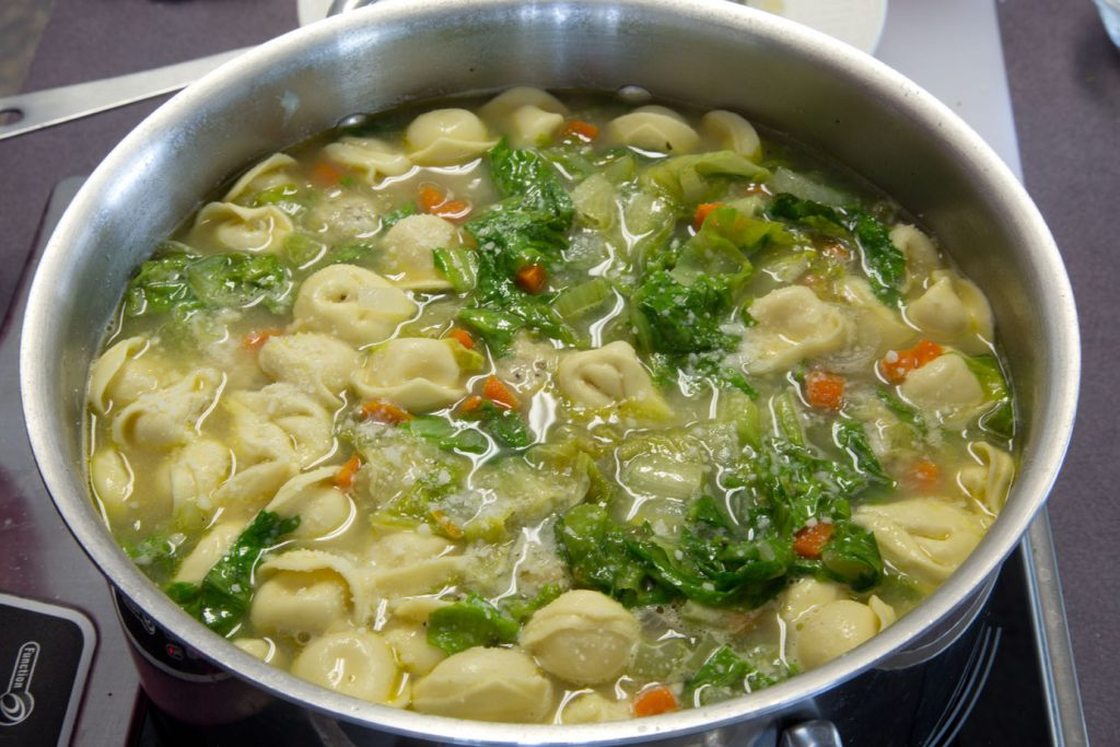 stock pot full of ingredients to make Italian wedding soup with tortellini and spinach