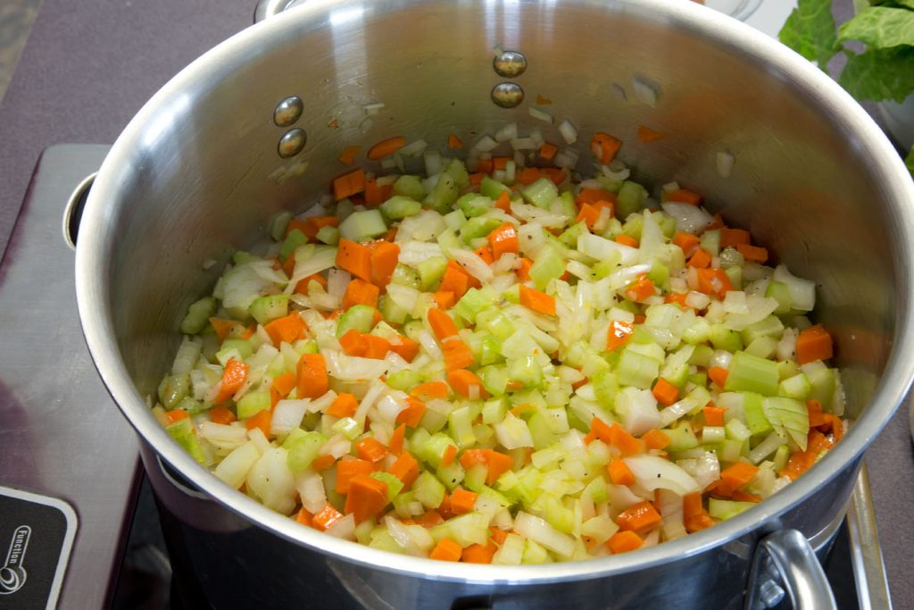 diced celery, carrots, and onion in a large stock pot simmering