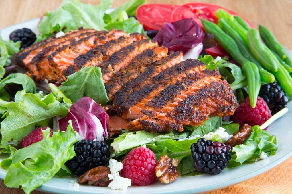 sliced filet of blackened salmon on a bed of lettuce with berries, nuts, green bean sand tomatoes