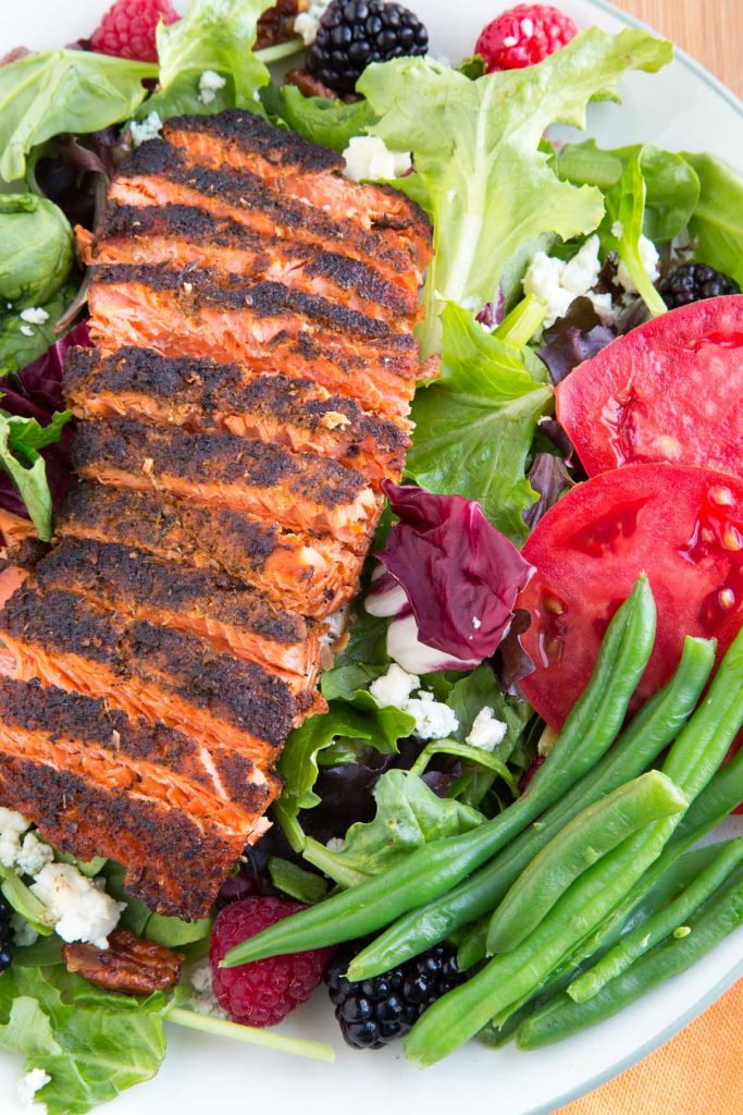 overhead partial view of sliced filet of blackened salmon on a bed of lettuce with berries, nuts, green bean sand tomatoes