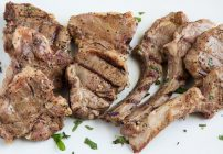 overhead view of grilled lamb chops on a white platter