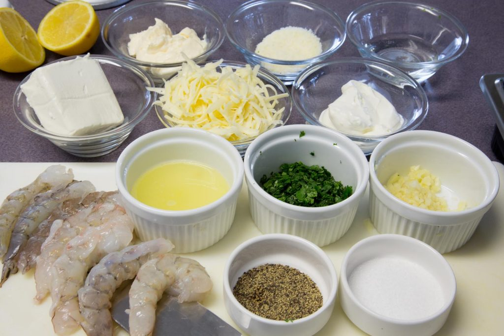 ingredients to make shrimp scampi dip in bowls and white ramikens