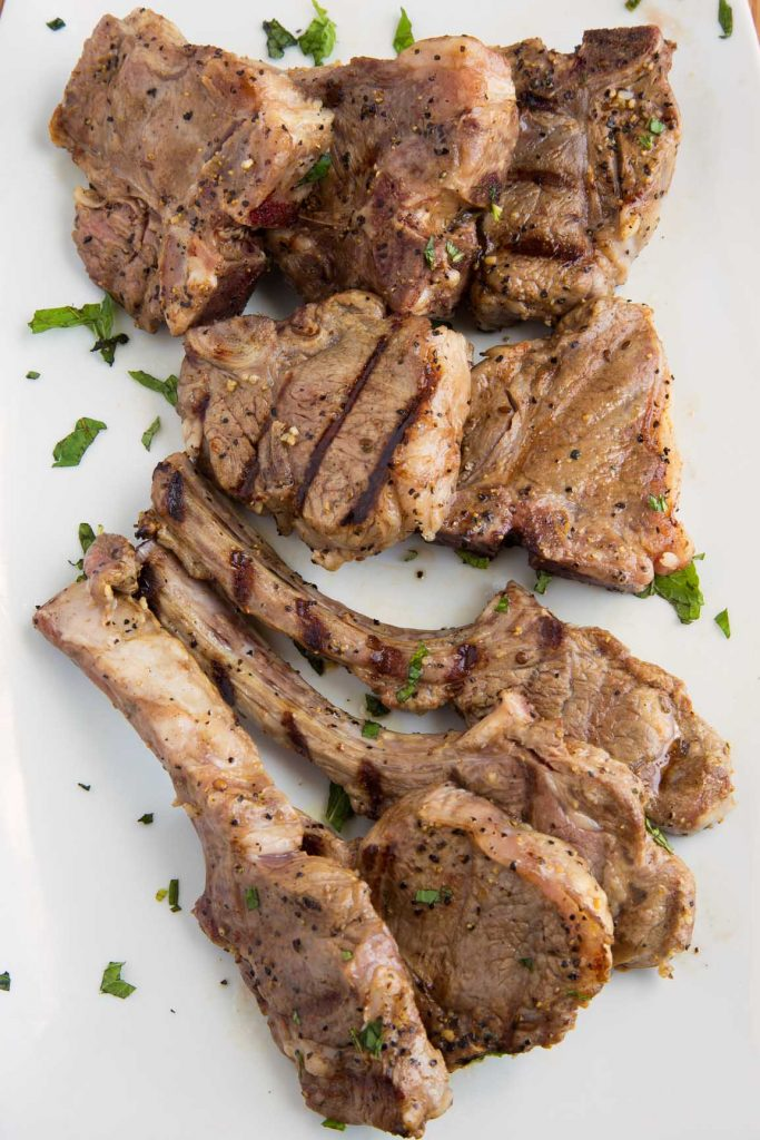 grilled lamb chops  on a white platter garnished with chopped parsley