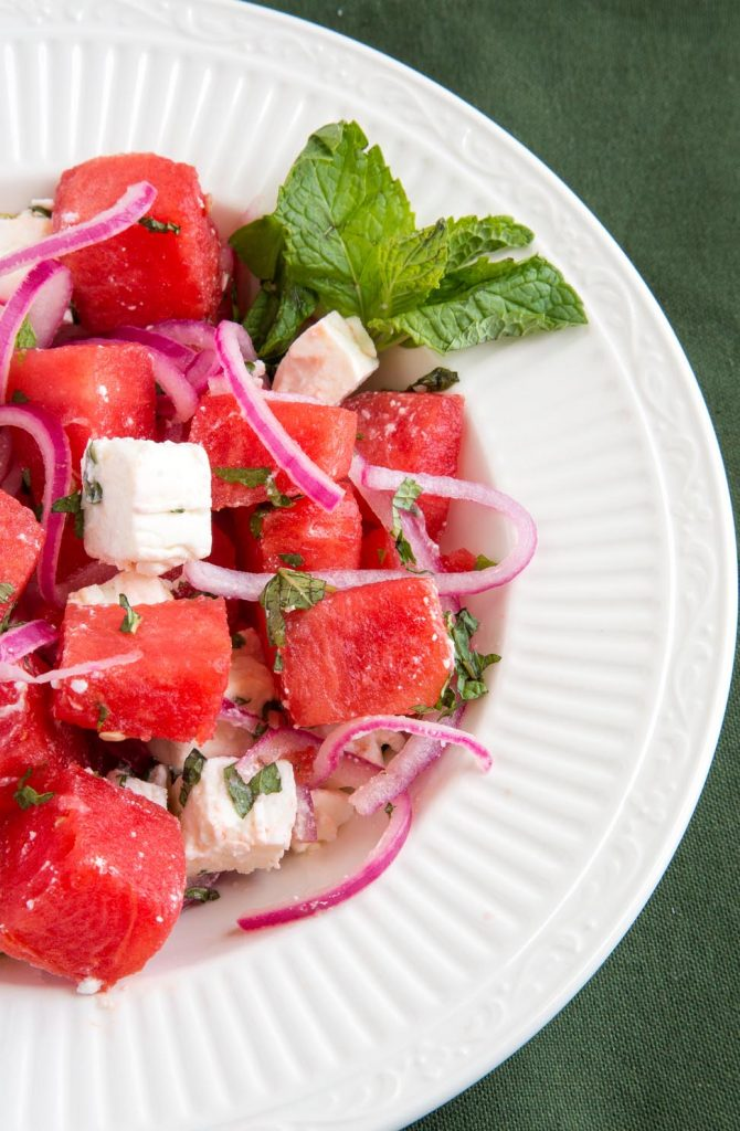 partial overhead shot of Watermelon feta salad with pickled onions in a white bowl