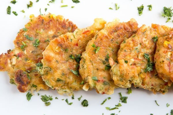 row of homemade corn fritters on a white platter sprinkled with parsley