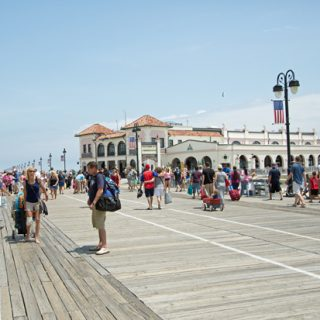 A group of people walking on the boardwalk in ocean city new jersey