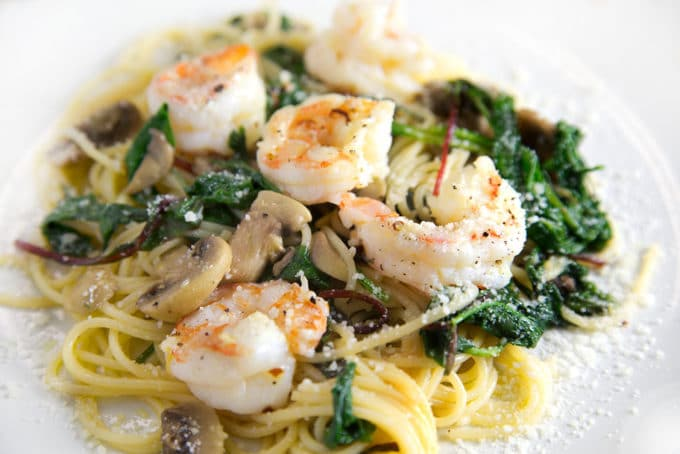Sautéed shrimp with Super greens and mushrooms on a white plate over pasta