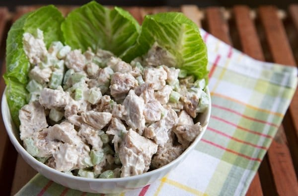 white bowl of chicken salad with lettuce leave sitting on a green striped napkin