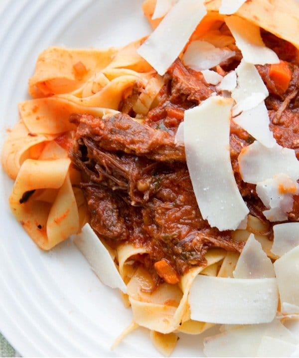 Wild Boar Ragu on Pappardelle pasta with shaved cheese slices on a white plate