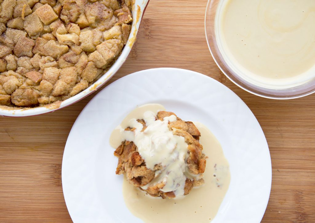 serving of caramel macchiato bread pudding next to a casserole of bread pudding and bowl of kahlua creme anglaise
