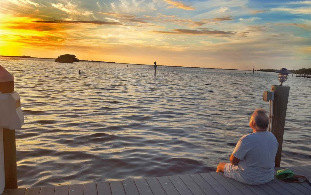 Chef Dennis sitting on the dock watching the sunset at Tarpon Lodge, Pine Island