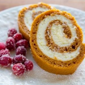 A close up of two slices of gluten-free pumpkin roll and candied cranberries