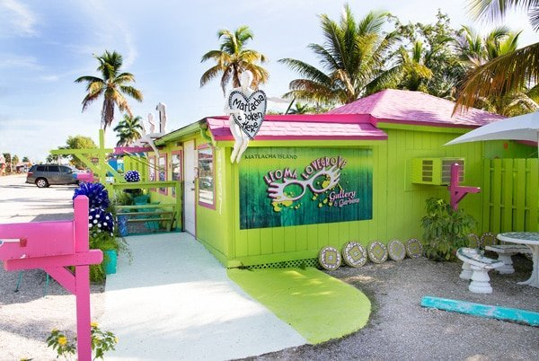 chartreuse color building with hot pink accents and palm trees in the background in Matlacha