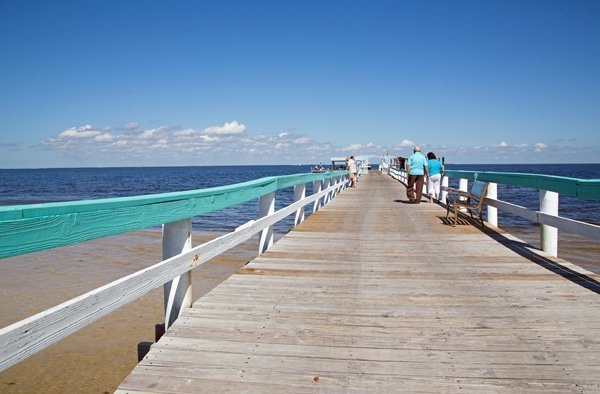 view down a long pier with blue skies