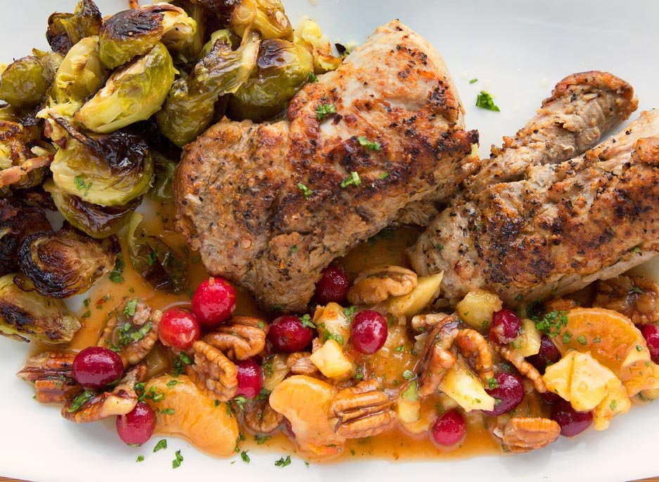 Peppered Pork Loin with a fruit and nut sauce and oven roasted Brussels Sprouts on a white plate