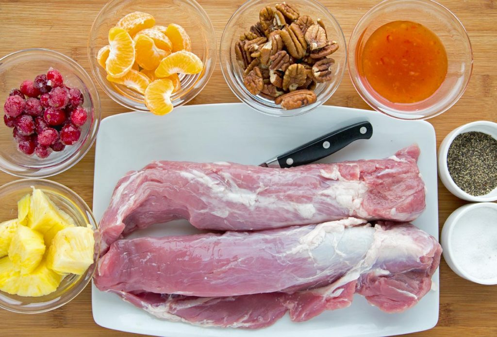 ingredients to make Peppered Pork Loin and sweet chili fruit and nut sauce sitting on a wooden cutting board