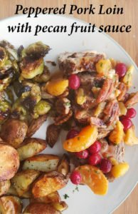 peppered pork loin with a sweet chili fruit sauce sitting on an off white plate with roasted potatoes and brussels sprouts