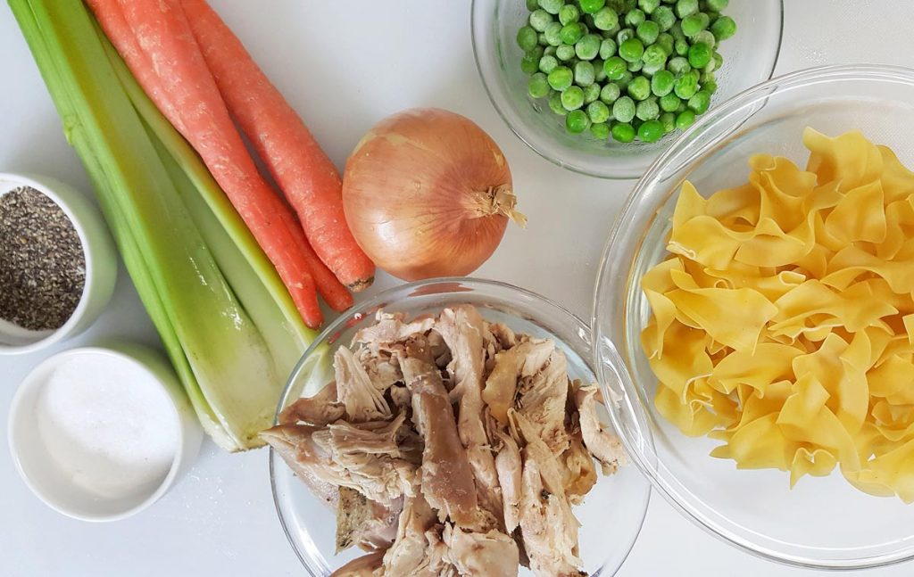ingredients to make turkey noodle soup on a white cutting board