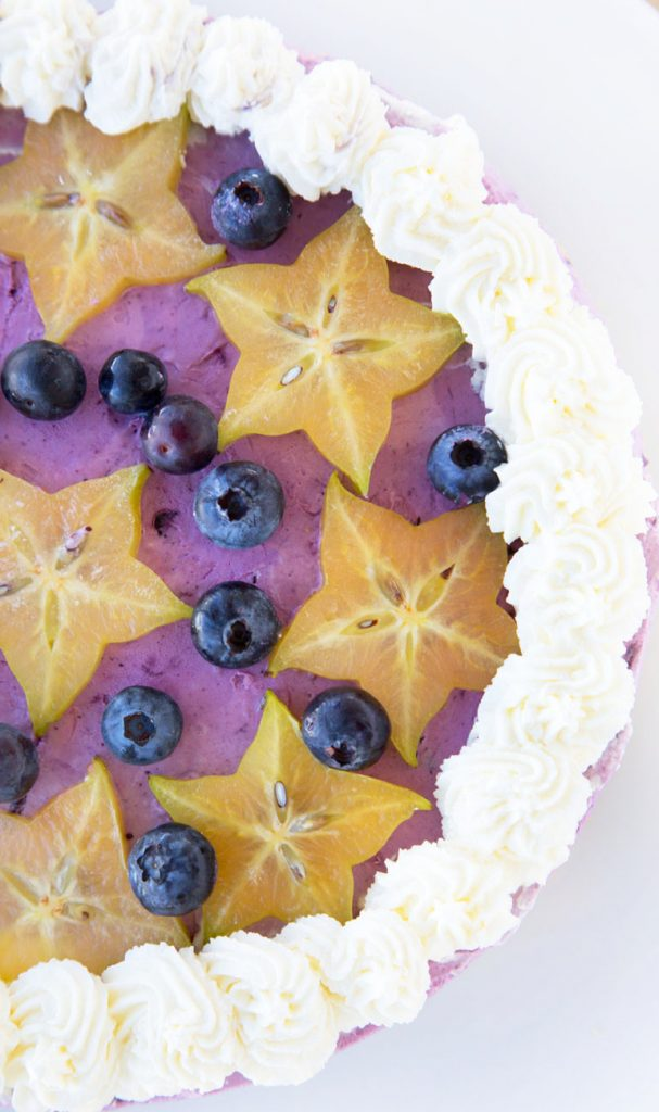 overhead partial view of a blueberry cream pie with star fruit slices and blueberries on top