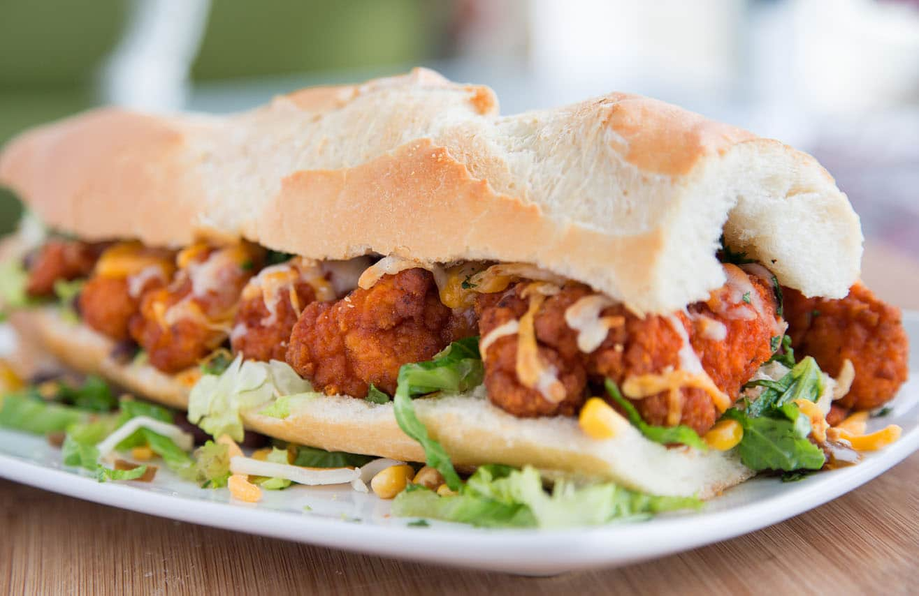 buffalo chicken po' boy sitting on a white plate on a cutting board