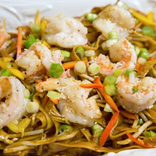 Chinese style dan dan noodles with shrimp on a white plate