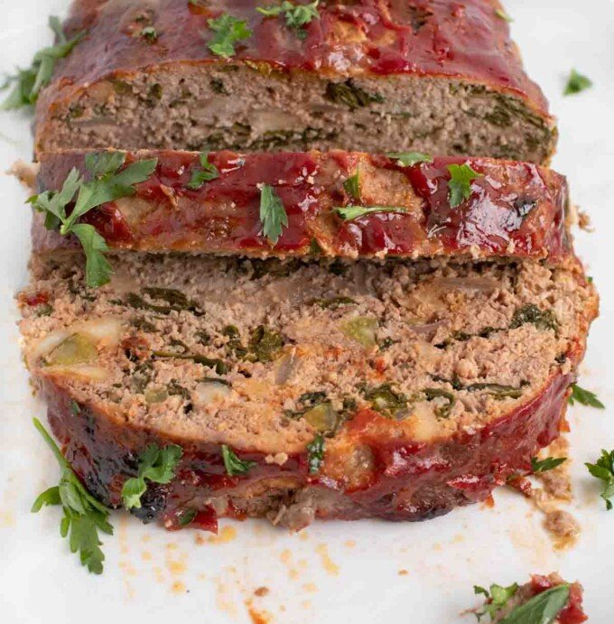 front view of sliced meatloaf on a white platter