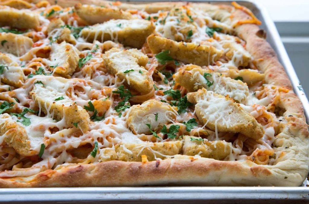 side view of a cooked sheet pan chicken parm pizza