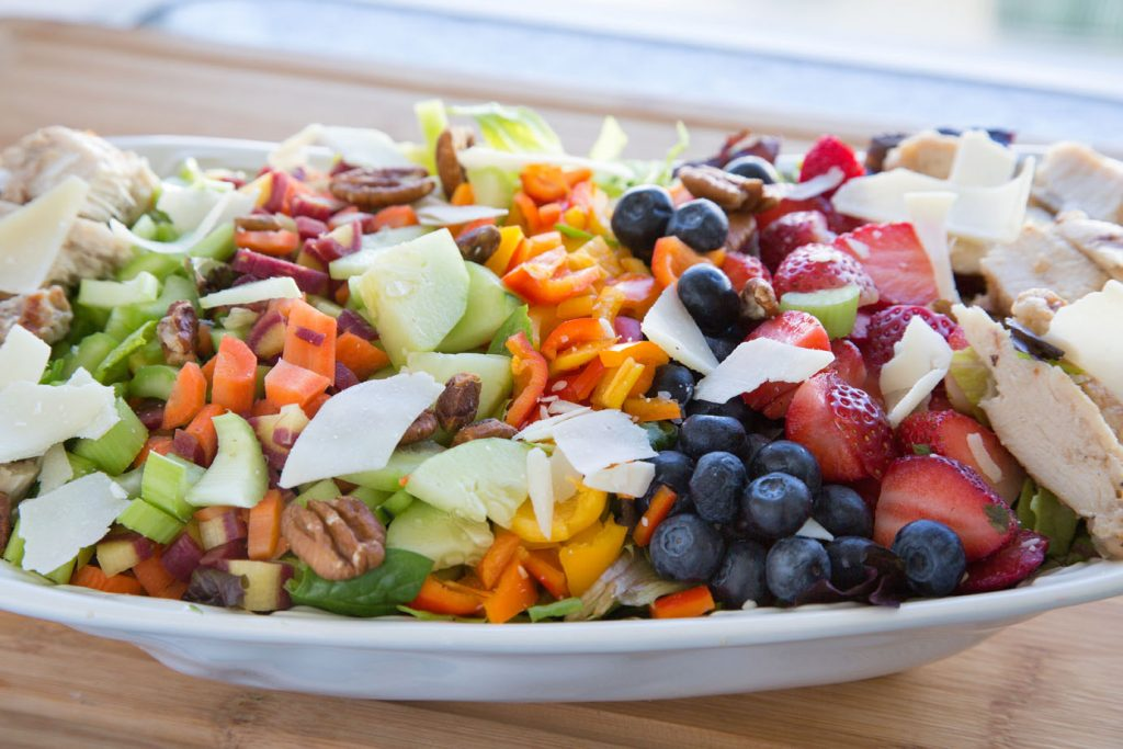 dinner salad with a variety of vegetables, berries , chicken, nuts and cheese on a bed of greens on a large white platter
