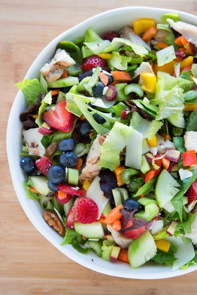 partial overhead view of a mixed summertime salad with berries, vegetables, nuts, chicken and cheese in a white bowl