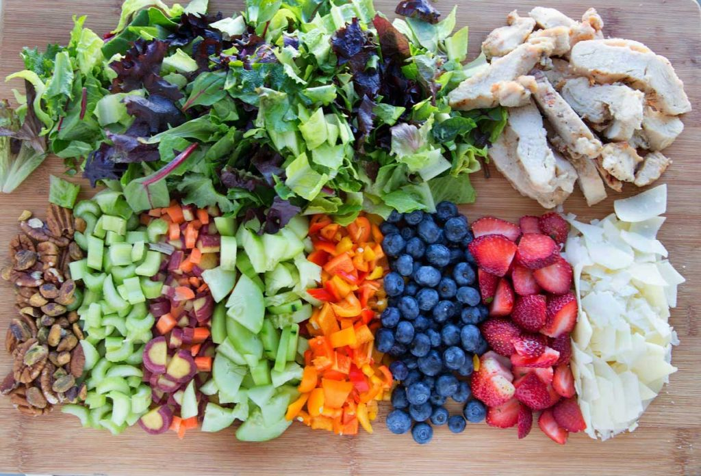 overhead view of ingredients to make the perfect dinner salad on a wooden cutting board